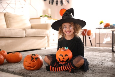 Cute little girl with pumpkin candy bucket wearing Halloween costume at home
