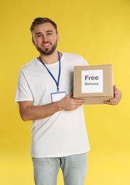 Male courier holding parcel with sticker Free Delivery on yellow background