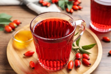 Fresh rose hip tea, honey and berries on wooden table, closeup