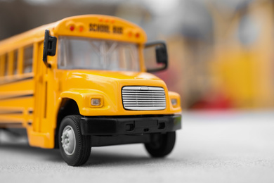 Yellow toy school bus against blurred  background, closeup. Transport for students