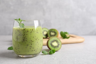 Delicious kiwi smoothie and fresh ingredients on light grey table, space for text
