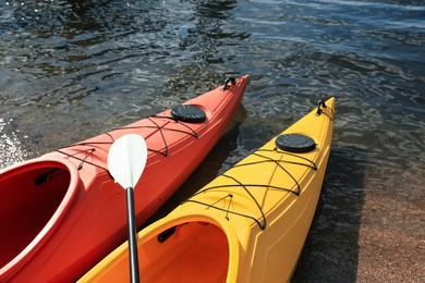 Modern kayaks with paddle on river, closeup. Summer camp activity