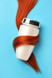 Bottle wrapped in lock of hair on light blue background, top view. Natural cosmetic product