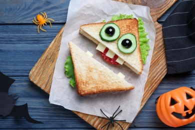 Cute monster sandwich served on blue wooden table, flat lay. Halloween party food