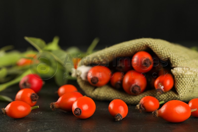 Ripe rose hip berries with green leaves on black table, closeup