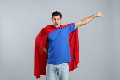Man wearing superhero cape on grey background