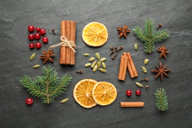 Flat lay composition with mulled wine ingredients and fir branches on black slate table