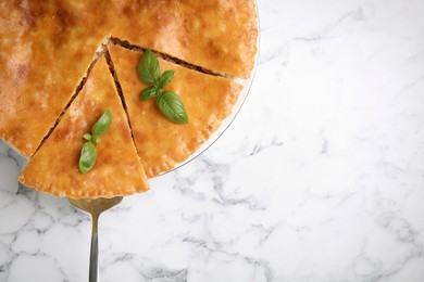 Delicious pie with meat and basil on white marble table, top view. Space for text