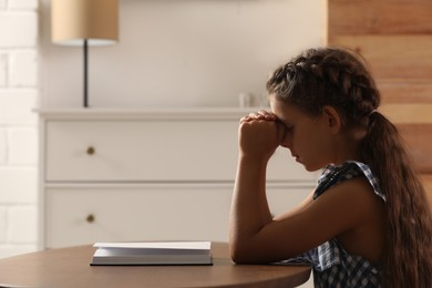 Cute little girl praying over Bible at table in room. Space for text
