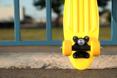 Modern yellow skateboard near fence outdoors, closeup. Space for text