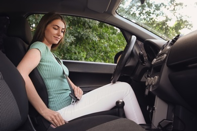 Young woman fastening safety belt on driver's seat in car