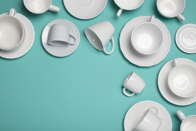 White cups and saucers on turquoise background, flat lay. Space for text