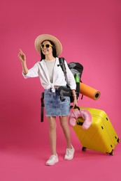 Female tourist with backpack, suitcase and travel pillow on pink background