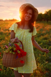 Woman with basket of poppies and wildflowers in beautiful field at sunset