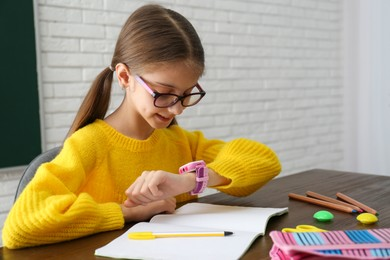 Girl with stylish smart watch at wooden table in school
