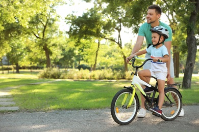 Happy father teaching his son to ride bicycle in park