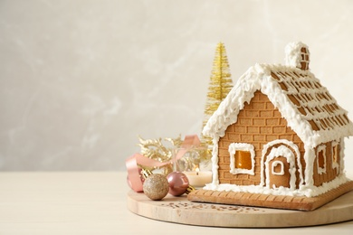 Beautiful gingerbread house decorated with icing and Christmas balls on table, space for text