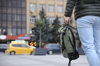 Male tourist with travel backpack on city street, closeup. Urban trip