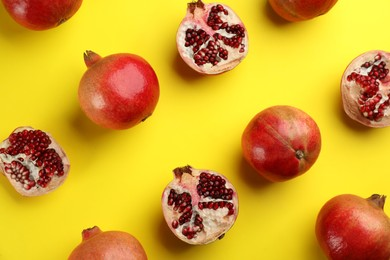 Flat lay composition with ripe pomegranates on yellow background