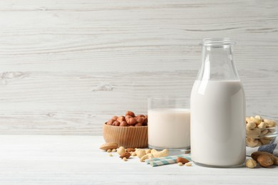 Different nut milks on white wooden table. Space for text