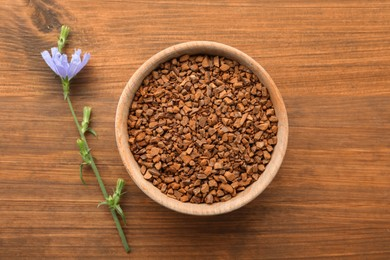 Bowl of chicory granules and flower on wooden table, flat lay