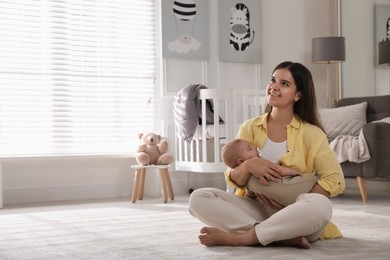 Young woman with her sleeping baby on floor at home