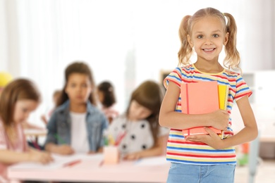 Happy little girl with notebooks in classroom