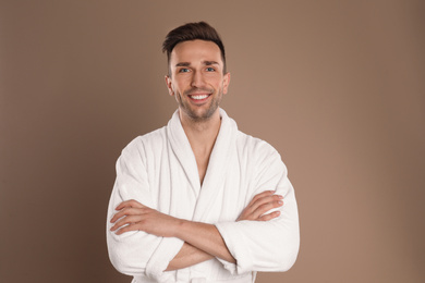 Happy young man in bathrobe on brown background