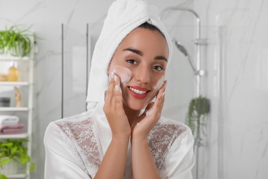 Beautiful young woman applying cleansing foam onto face in bathroom. Skin care cosmetic