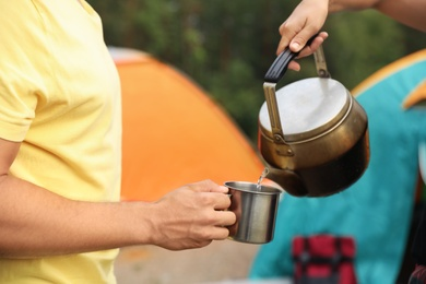 Woman pouring drink into mug for man outdoors. Camping season