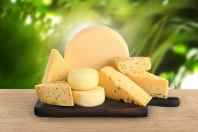 Different types of delicious cheeses on wooden table outdoors. Dairy products