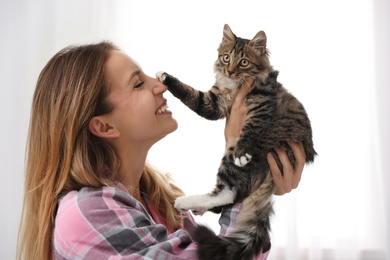 Woman wearing pajama with cat at home. Owner and pet