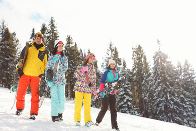 Group of friends with equipment on snowy slope. Winter vacation