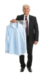 Senior man holding hanger with shirt in plastic bag on white background. Dry-cleaning service