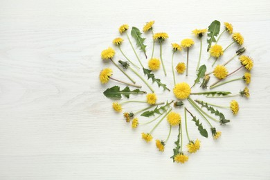 Heart made of beautiful yellow dandelions on white wooden table, flat lay. Space for text