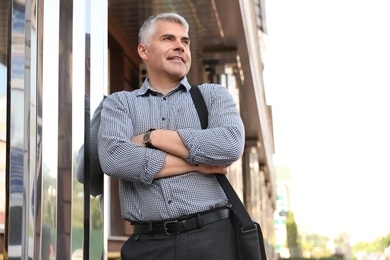 Portrait of handsome businessman in city, space for text