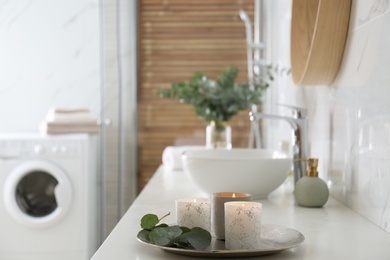 Tray with eucalyptus leaves and burning candles on countertop in bathroom