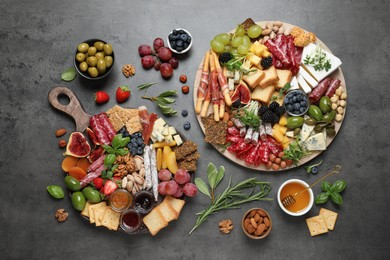 Different tasty appetizers on dark grey table, flat lay
