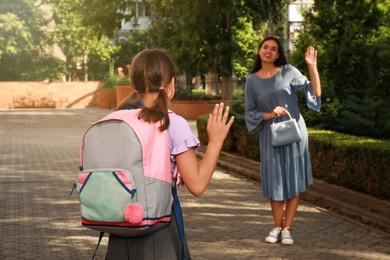 Mother waving goodbye to her daughter before school outdoors
