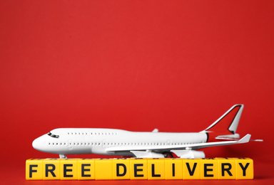 Toy plane and cubes with words FREE DELIVERY on red background, space for text. Logistics and wholesale concept