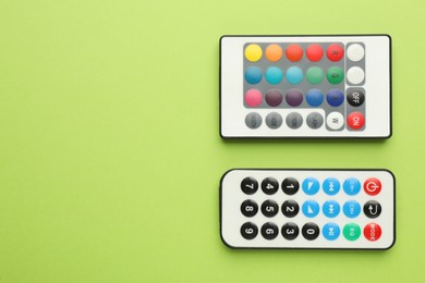 Remote controls on light green background, flat lay. Space for text