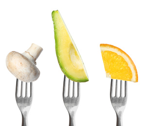 Forks with different vegetables and fruits on white background. Healthy meal