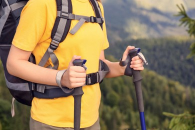 Woman with backpack and trekking poles hiking in mountains, closeup
