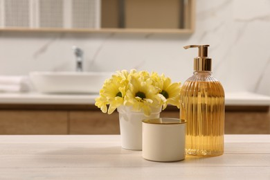Glass dispenser with liquid soap, candle holder and beautiful flowers on white table in bathroom, space for text
