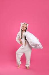 Cute girl wearing pajamas with pillow on pink background