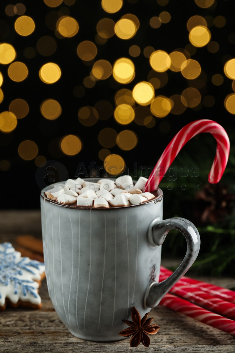 Delicious hot chocolate with marshmallows and candy cane on wooden table against blurred lights