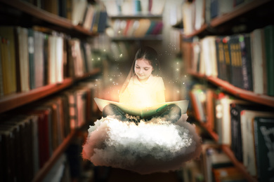 Cute little girl reading magic book in library
