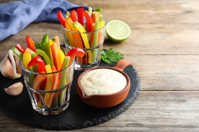 Fresh raw vegetable sticks and sauce on wooden table