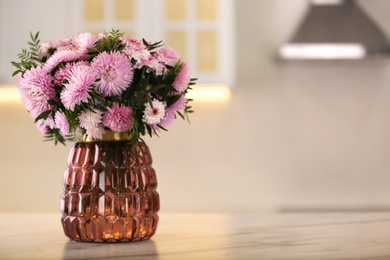 Vase with beautiful chrysanthemum flowers on table in kitchen, space for text. Interior design