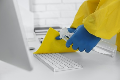 Employee in protective suit and gloves sanitizing keyboard indoors, closeup. Medical disinfection